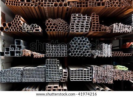 A series of different sizes metal pipes on  shelf - stock photo