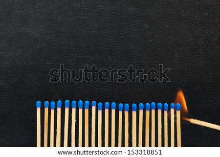 A series of matches are next to each other, which burn one after another. - stock photo