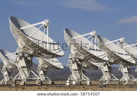 A series of radio telescope dishes looking skyward. - stock photo