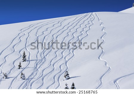 a series of ski tracks through fresh powder snow down a hill side - stock photo