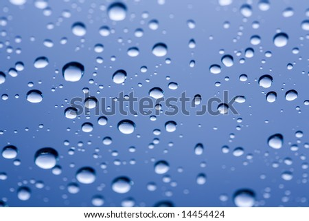 A series of water drops on a sheet of glass - stock photo
