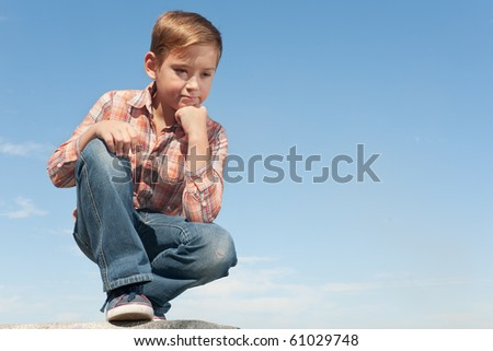 A serious boy is thinking about childish problems sitting against the sky - stock photo