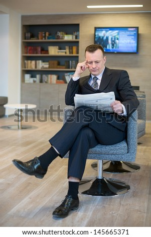A serious businessman in a suit and tie reading a newspaper