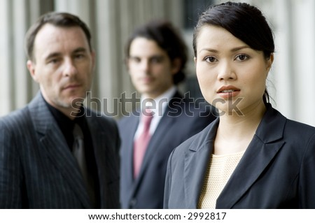 A serious businesswoman standing in front of two male colleagues (shallow depth of field used)