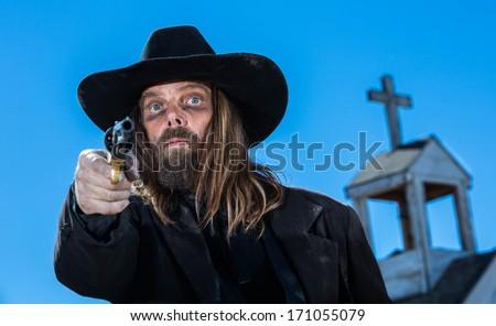 A serious cowboy holding a gun near a church - stock photo