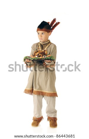 A serious elementary boy carrying a wooden plate with roasted fowl and vegetables while dressed as a native American.  Isolated on white. - stock photo