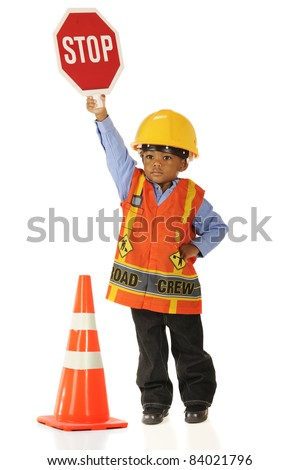 A serious little boy in road crew gear holding a stop sign high.  Isolated on white. - stock photo