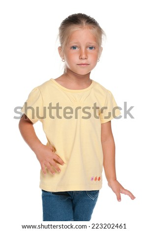 A serious little girl stands against the white background