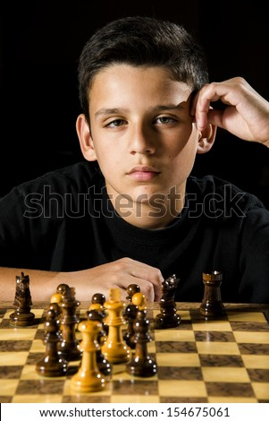 a serious looking boy stares at his opponent during a chess game.  - stock photo