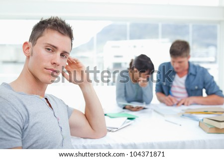 A serious looking student sits looking into the camera with his hand on his head as his friends work behind him