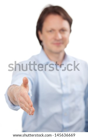 A serious man in shirtsleeves offers his hand in a handshake as a sign of sincerity in sealing a business deal, in greeting or offering his congratulations - stock photo