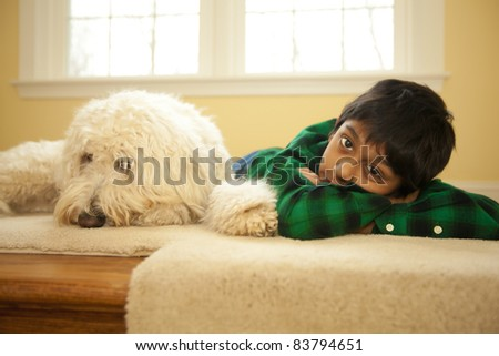 A serious portrait of a boy and his dog. - stock photo