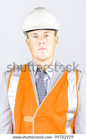 A serious responsible young man in the high visibility orange jacket and hard hat, representing a health and safety officer going about an inspection to ensure safe working conditions - stock photo