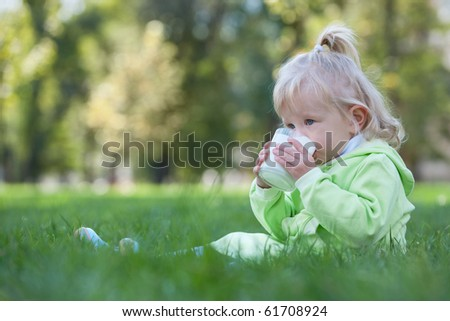 A serious toddler is drinking milk from a glass sitting on the grass - stock photo