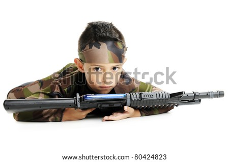 A serious young boy in army camouflage, crawling on his belly with a black machine gun.  Isolated on white. - stock photo