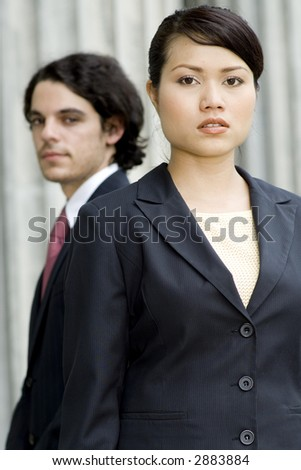 A serious young businesswoman standing in front of a male colleague