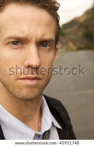 A serious young man looking at camera