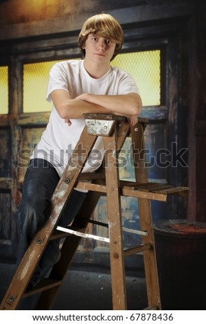 A serious young teen boy on a ladder in an old garage.