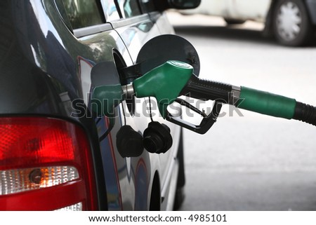 A service station gas nozzle in the fuel filling hole of a car. focus on the handle