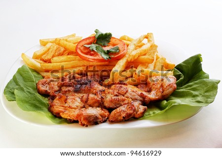 A serving dish piled with roast lemon chicken thighs and French fries, or chips, with a serving spoon - stock photo