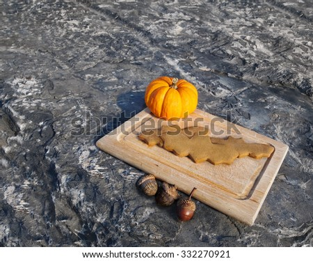 A serving of bat shaped gingerbread cookies on a cutting board with a miniature pumpkin and some acorns.  - stock photo