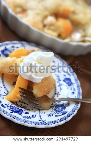 A serving of fresh peach cobbler with whipped cream, rest of cobbler in background - stock photo