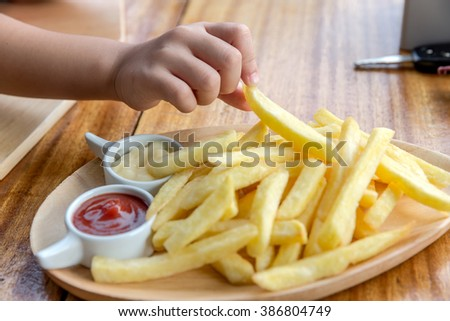 A Serving of fries, French fries with ketchup on wooden background - stock photo