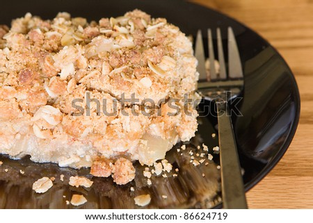 a serving of homemade apple crisp on a plate with a fork - stock photo