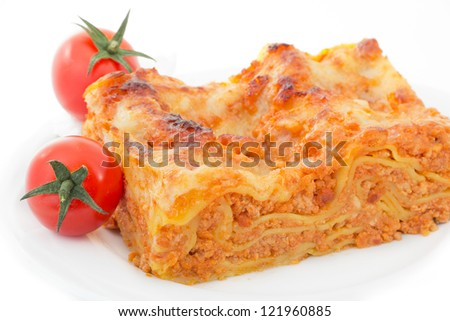 A serving of lasagna on a plate with tomatoes