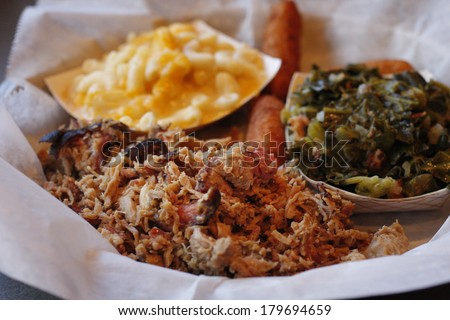 A serving of pulled pork with side dishes of Macaroni and cheese,  collard greens, and fried hush puppies. - stock photo