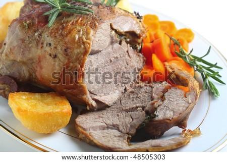 A serving plate with a joint of roasted boneless lamb roasted potatoes and boiled carrots, garnished with sprigs of rosemary
