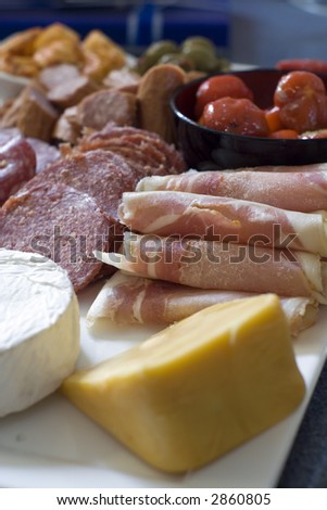 A serving platter filled with sliced salami, kabana, stuffed peppers, dried tomato, rolled prosciutto, pancetta, brie and cheddar cheese. - stock photo