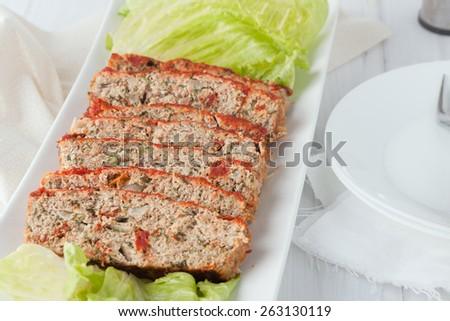 a serving platter of sliced turkey meatloaf with spinach and sun dried tomatoes  - stock photo