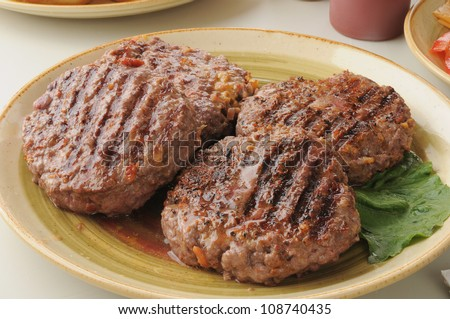 A serving platter of thick juicy grilled hamburger patties stuffed with cheddar cheese - stock photo