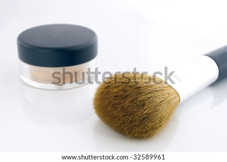 A set of a big makeup brush and a jar of mineral foundation.
