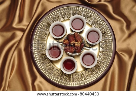 A set of arabic tea cups with dates. - stock photo