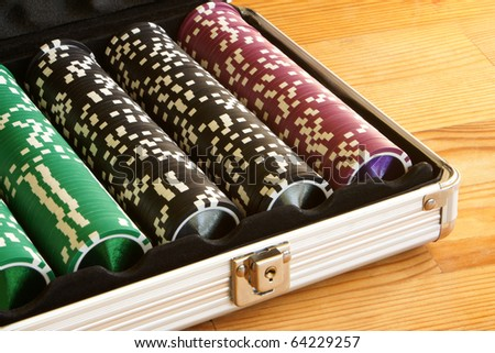 A set of casino chips on a wooden table - stock photo
