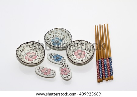 a set of ceramic bowl and chop sticks on a white background - stock photo