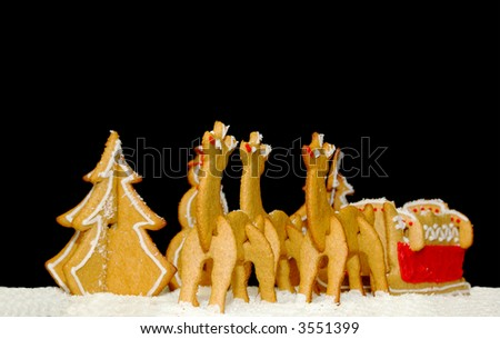 A set of Christmas gingerbread cookies on a black background - reindeer pulling a sleigh with a pine and a snowman in the background.
