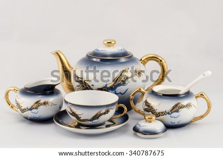 A set of coffee cups, sugar bowl, jug. Set coffee with the design of a dragon. Blue, white and gold. - stock photo