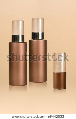 A set of cosmetic bottles over the beige background - stock photo