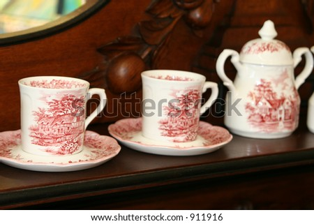 A set of cups, saucers and tea or coffee pot grace an antique oak sideboard. - stock photo