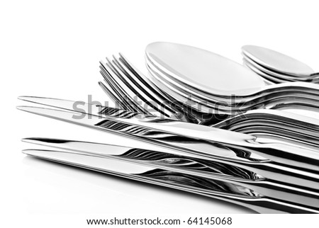 a Set of cutlery with stacked knifes, forks, spoons and tea spoons on a white background with space for text - stock photo