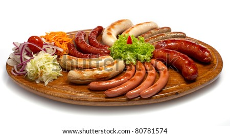 a set of different sausages, grilled on wooden plate - stock photo