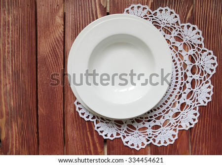 A set of dining plates on lacy napkin.Rustic wooden table background.