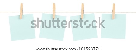 A set of four blank blue sticky notes held on a string with clothespins isolated on white. - stock photo