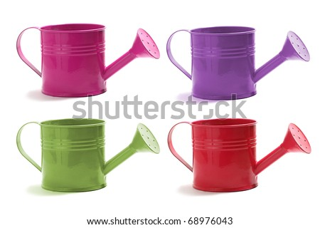 A set of four watering cans isolated on white in red, green,violet, and pink. - stock photo