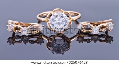 A set of gold jewelry: earrings and ring with gemstone