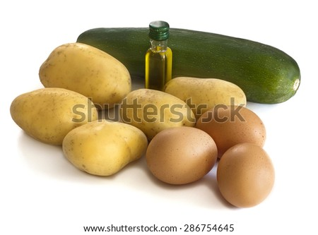 A set of ingredients for a traditional Spanish tortilla: four potatoes, three eggs, one zucchini and a bit of olive oil, on white background - stock photo