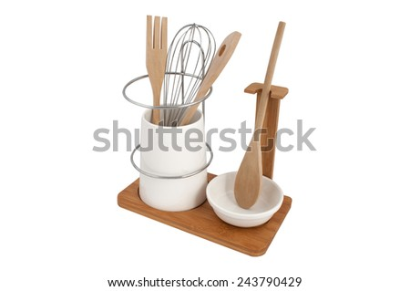 a set of kitchen tools in a ceramic Cup on a wooden stand isolated on white background